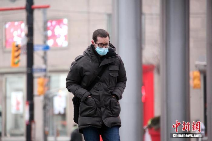"""资料图:当地时间1月14日,佩戴口罩的民众行走在加拿大多伦多市中心街头。多伦多所在的加拿大人口第一大省安大略省从当天开始实施""""居家令""""。该省已于12日宣布再次进入持续至少28天的省级紧急状态,以遏制严峻疫情。 中新社记者 余瑞冬 摄"""