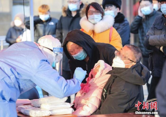 1月18日,北京大兴区启动天宫院街道及周边5个街道、2个基地的全员核酸检测工作,预计检测52.2万人。1月17日0时至24时,北京新增2例本地确诊病例,均住大兴区天宫院街道。图为大兴区高米店街道的一处采样点,工作人员对居民进行核酸检测采样。 中新社记者 赵隽 摄