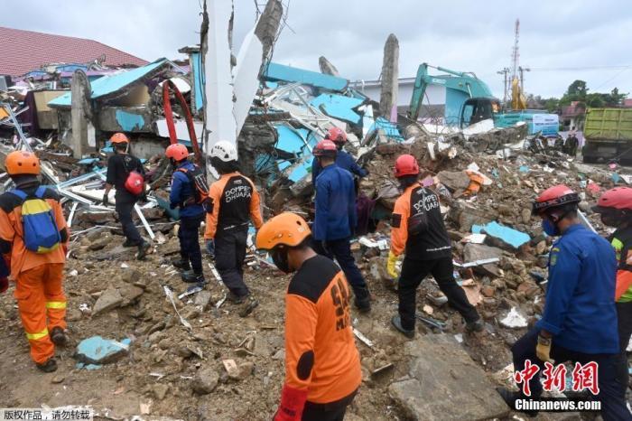 1月17日,印尼西苏拉威西省,印尼警察带着K9嗅探犬检查地震后倒塌的医院大楼。