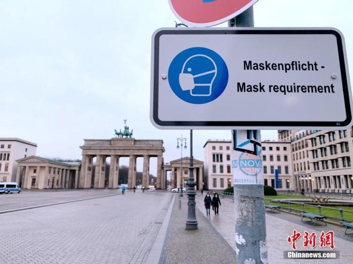 资料图:德国柏林勃兰登堡门前的佩戴口罩提示牌。中新社记者 彭大伟 摄
