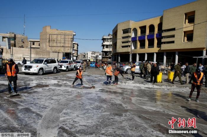 当地时间1月21日,伊拉克巴克达市中心发生自杀式爆炸袭击。图为工作人员正在清理爆炸现场。