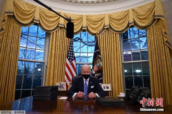 当地时间1月20日中午,美国当选总统、民主党人拜登在国会山正式宣誓就任美国第46任总统。图为美国总统拜登在华盛顿白宫椭圆形办公室签署行政命令。