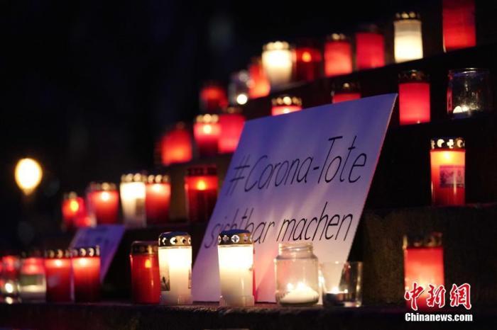 """2020年12月,德国的记者和艺术家发起了一项名为""""让新冠逝者被看见""""的行动,呼吁人们每周日在自己城市点亮蜡烛,悼念那些因感染新冠病毒去世的人。截至今年1月24日,德国已有超过5万人死于新冠病毒感染。图为1月24日晚,柏林阿恩斯瓦尔德广场一处台阶摆满蜡烛,并放上了""""让新冠逝者被看见""""字样的牌子。 中新社记者 彭大伟 摄"""