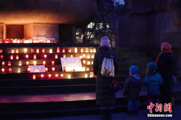 图为1月24日晚,人们在柏林阿恩斯瓦尔德广场摆放的蜡烛前驻足。 <a target='_blank' href='http://www.chinanews.com/'>中新社</a>记者 彭大伟 摄
