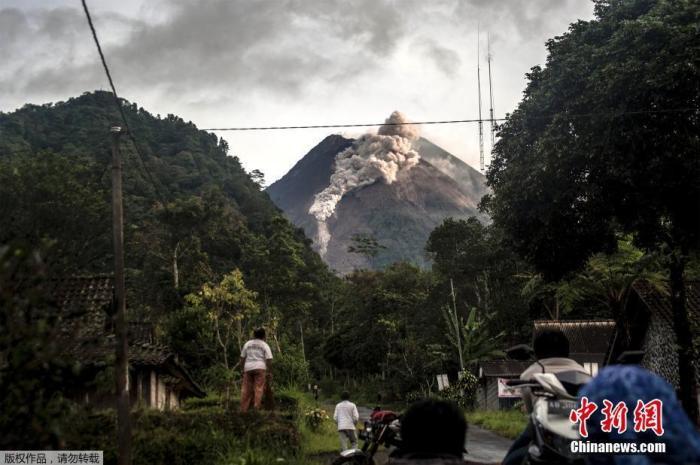 当地时间1月27日,印度尼西亚日惹省,默拉皮火山喷发出岩石和火山灰,顶部冒出滚滚浓烟,火山附近的民众纷纷在路边围观这一景象。