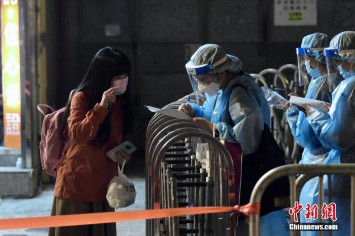 """1月28日晚上,香港特區政府在北角指明""""受限區域"""",即錦屏街東發大廈A、B、C和D座內的人士須留在其處所并按特區政府安排接受強制檢測。圖為居民登記返回處所。 <a target='_blank' href='http://www.jiaojiaomei.com/'>中新社</a>記者 李志華 攝"""