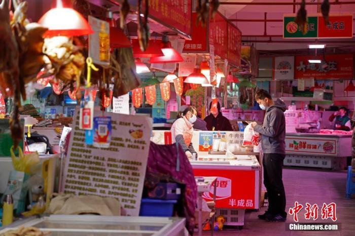 资料图:市民在农贸市场内选购食品。 殷立勤 摄