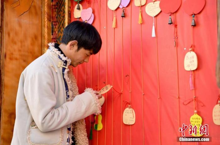 图为在理塘勒通古镇街头许愿墙前,丁真观看游客们的留言。(资料图片) 中新社记者 刘忠俊 摄