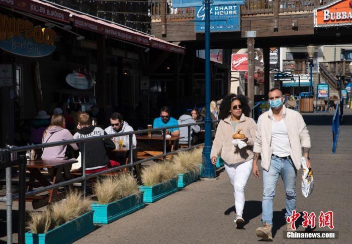 """当地时间2月5日,民众在美国加州旧金山知名景点39号码头用餐。加州于今年1月下旬解除了""""居家令""""限制,各县的餐厅以及个人护理等商业可以重新开放。 记者 刘关关 摄"""