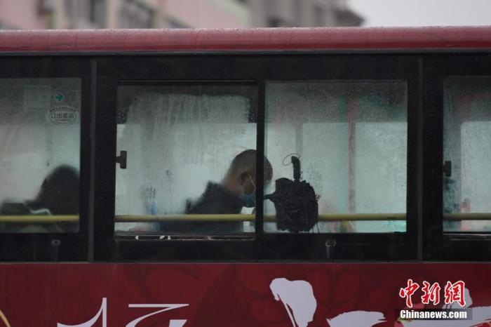资料图:乘车市民将雨伞放在窗边。 中新社记者 刘冉阳 摄