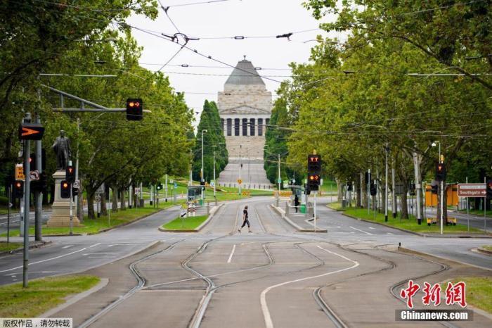 """當地時間2月13日,澳大利亞墨爾本,行人走在空曠的城市街道上。澳大利亞維多利亞州因本地疫情出現蔓延勢頭而宣布""""封城""""5天。州長安德魯斯12日在新聞發布會上表示,該州從13日凌晨開始實施5天的四級管控。在新的管控措施下,所有民眾除了采購生活和醫療必需品、必要的工作和學習、照顧別人、每天兩小時的鍛煉以外,必須待在家中。正在該州首府墨爾本舉行的2021年澳網也因此從13日起取消觀眾現場觀賽,直到相關管控措施結束。"""