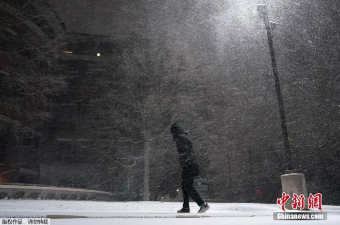 当地时间2月15日,美国得克萨斯州遭遇冬季风暴袭击,全州气温均低于零摄氏度。图为一名行人走在暴风雪中。