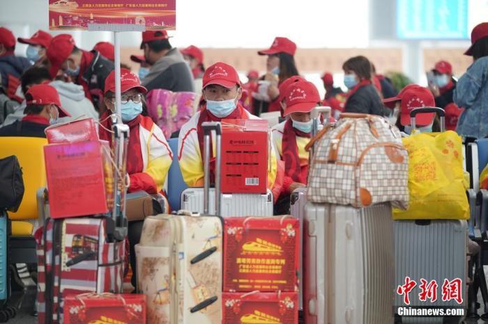 资料图:乘坐专列的务工人员在专用候车区等待上车。中新社记者 刘冉阳 摄