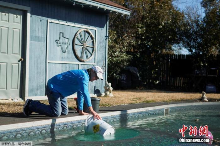 当地时间2月20日,由于美国得州遭遇暴风雪极寒天气,部分地区水电供应紧张,家住得州的罗德尼・罗伯茨从自家的泳池里打水用于厕所冲马桶。