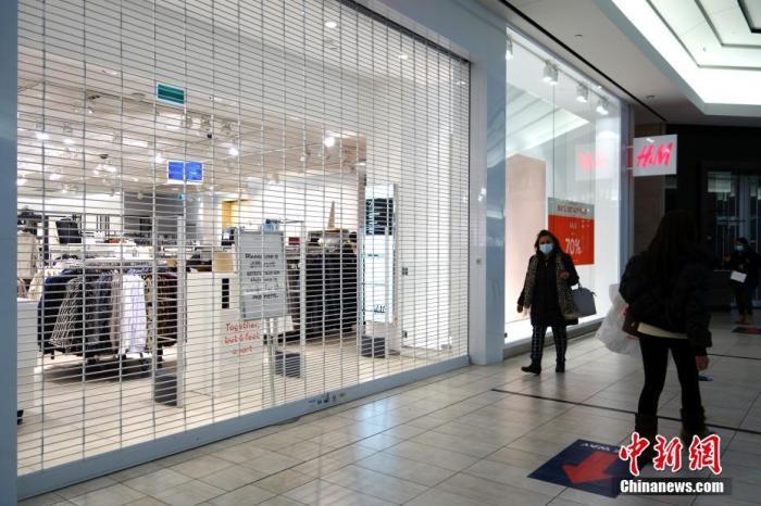 """当地时间2月22日,加拿大安大略省华人聚居区万锦市(Markham),一家服装店虽然当日重开,但为限制人流,并未打开所有入口。随着始于去年秋季的第二波疫情现已出现明显受控迹象,加拿大多地正尝试放宽限制措施。在累计病例数最多的安大略省,22日又有多个地区解除""""封城"""",包括万锦市所属的、毗邻多伦多的约克区等,但多伦多现仍实行""""居家令""""。 中新社记者 余瑞冬 摄"""