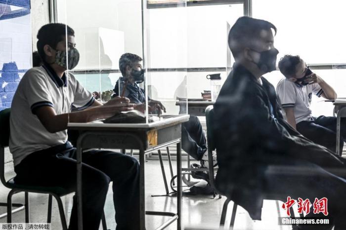 资料图:哥伦比亚Itagui一所学校,为防范疫情,学生们戴口罩在设置的挡板里听课学习。