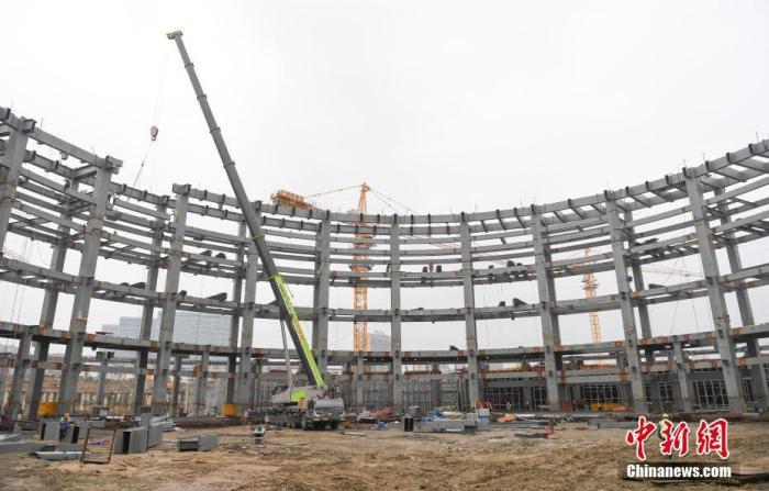 """2月27日,浙江杭州,多名工人在搭建競技場館鋼架結構。春節后,杭州2022年亞運會電子競技場館進入緊張建設中,400多名工人24小時不間斷輪崗作業。截至目前,場館建設已完成全部樁基工程,地下室施工完成60%。據了解,該場館外觀以""""星際漩渦""""為設計理念,總建筑面積約8萬平方米,有大約4087個座位。 <a target='_blank' href='http://www.a4ck.com/'>中新社</a>記者 王剛 攝"""