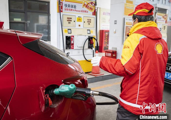 """3月2日,北京市朝阳区一处加油站的工作人员给车辆加油。按照中国国内成品油调价规则,新一轮成品油零售限价调整窗口将于3月3日24时开启,推测油价将会成为2021年的第四次上涨,并形成""""八连涨""""的态势,将创现行国内成品油价格形成机制实施以来最长的连续油价上调次数新纪录。 中新社记者 侯宇 摄"""