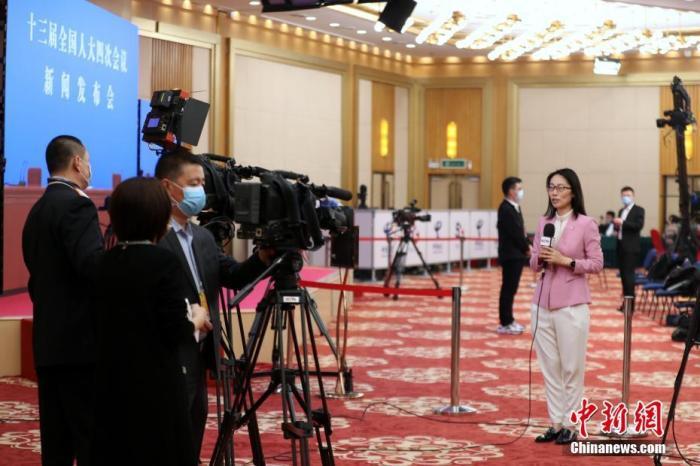 3月4日晚,十三届全国人大四次会议新闻发布会在北京人民大会堂新闻发布厅举行,大会发言人张业遂就会议议程和人大有关工作回答中外记者提问。为有效防控疫情,共同维护公共卫生与健康,新闻发布会采用网络视频形式进行。图为新闻发布会开始前,央视记者在分会场梅地亚中心内进行直播。 中新社记者 蒋启明 摄