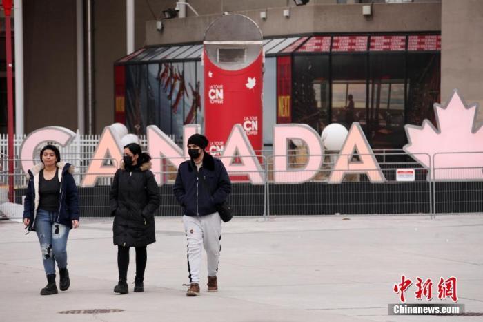 """当地时间3月8日,加拿大多伦多,行人从市中心的""""加拿大""""字样灯牌前经过。多伦多等地区从当日起取消实施了52天的""""居家令"""",从而使""""居家令""""在累计病例数居加拿大之首的安大略省全面取消。中新社记者 余瑞冬 摄"""