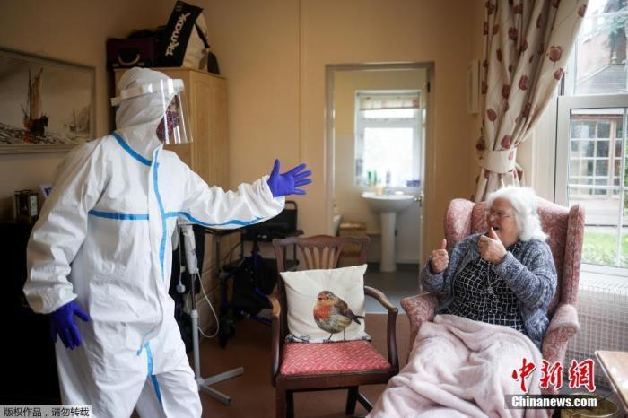 当地时间3月8日,英国伦敦部分养老院开始接受亲人探望,图为身穿防护服的尼基·克劳夫与母亲见面。