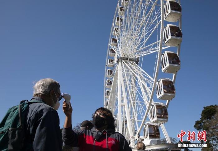当地时间3月12日,在美国加利福尼亚州旧金山金门公园准备乘坐摩天轮的顾客接受体温检测。日前,旧金山包括摩天轮在内的多种设施陆续重新开放。 中新社记者 刘关关 摄