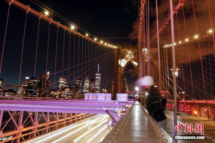 当地时间3月14日晚,美国纽约市政府将因新冠肺炎去世的患者面容投影在布鲁克林大桥桥身上,表达对逝者的怀念。当晚,纽约市举行活动纪念因新冠肺炎去世的患者。 中新社记者 廖攀 摄