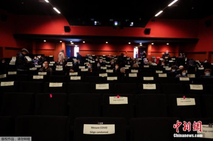 当地时间3月14日,法国巴黎南部Ivry-sur-Seine,民众按照防疫要求佩戴口罩进入电影院,隔位就坐观赏电影。