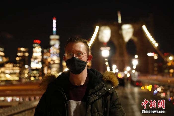 当地时间3月14日晚,美国纽约市政府将因新冠肺炎去世的患者面容投影在布鲁克林大桥桥身上  ,表达对逝者的怀念 。当晚,纽约市举行活动纪念因新冠肺炎去世的患者  。图为百老汇艺人布兰登·伍兹来到大桥前怀念因新冠肺炎去世的朋友 。 <a target='_blank' href='http://www.leosquarez.com/'>中新社</a>记者 廖攀 摄