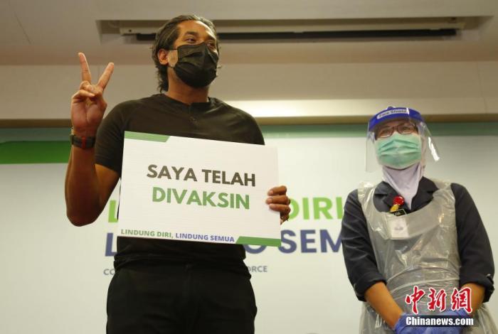 """3月18日起,马来西亚开始接种中国科兴生物生产的新冠疫苗,马来西亚科学、工艺及创新部部长凯里·贾马鲁丁成为科兴新冠疫苗在该国首位接种者。图为在森美兰州一家医院,凯里(左)接种疫苗后举起写有马来文""""我接种了疫苗""""的牌子。 中新社发 温俊钦 摄"""