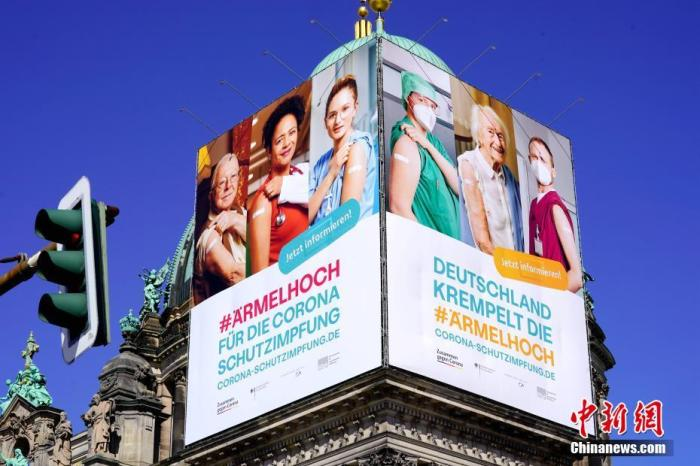 """经过彻夜会谈,德国总理默克尔最终于当地时间3月23日凌晨2时许宣布与各州达成决议,将目前实施的""""封城""""措施延至4月18日。因应当前严峻的第三波新冠疫情,德国将在4月第一周的复活节假期实施自疫情暴发以来最为严厉的限制措施。图为22日下午拍摄的柏林大教堂上的巨幅疫苗接种广告。 中新社记者 彭大伟 摄"""