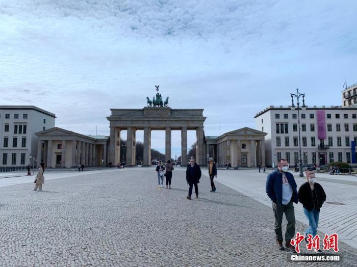 资料图:戴口罩的路人经过柏林地标勃兰登堡门。 中新社记者 彭大伟 摄