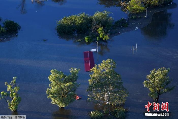 当地时间3月24日,澳大利亚悉尼附近的温莎地区,航拍画面显示洪水几乎淹没房屋,隐约能看到些许房屋屋顶在水面之上。
