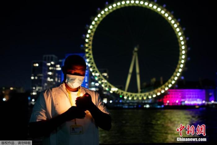 """内地时间2021年3月23日,英国伦敦,英国地标和修建亮起黄色灯光,眷念首次""""封城""""一周年。图为位于秦晤士河边的伦敦眼亮起黄灯。"""