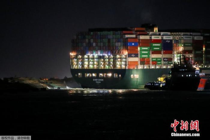 当地时间3月27日,埃及苏伊士运河,搁浅的集装箱船在深夜灯火通明。