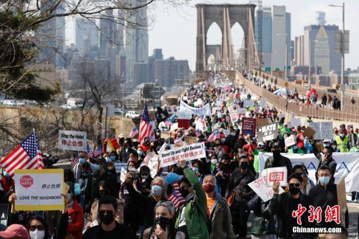 当地时间4月4日,纽约举行反仇恨亚裔大游行,上万民众手持标语在曼哈顿弗利广场集会后,游行穿过布鲁克林大桥至布鲁克林卡德曼广场。图为民众游行穿过布鲁克林大桥。 <a target='_blank' href='http://www.chinanews.com/'><p  align=