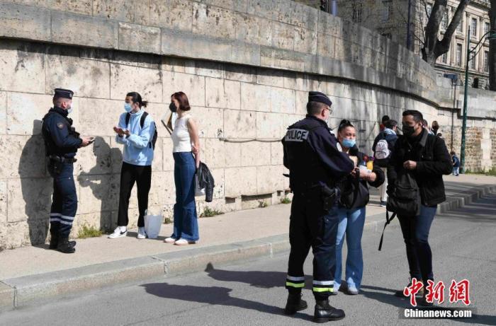 """当地时间4月4日,法国处于复活节假期期间,而巴黎处于""""封城""""中。为遏制新冠疫情恶化,目前法国本土全境已采取""""封城""""措施。图为警察在巴黎塞纳河沿岸对民众的出行证明等文件进行抽查。 <a target='_blank' href='http://www.chinanews.com/'>中新社</a>记者 李洋 摄"""
