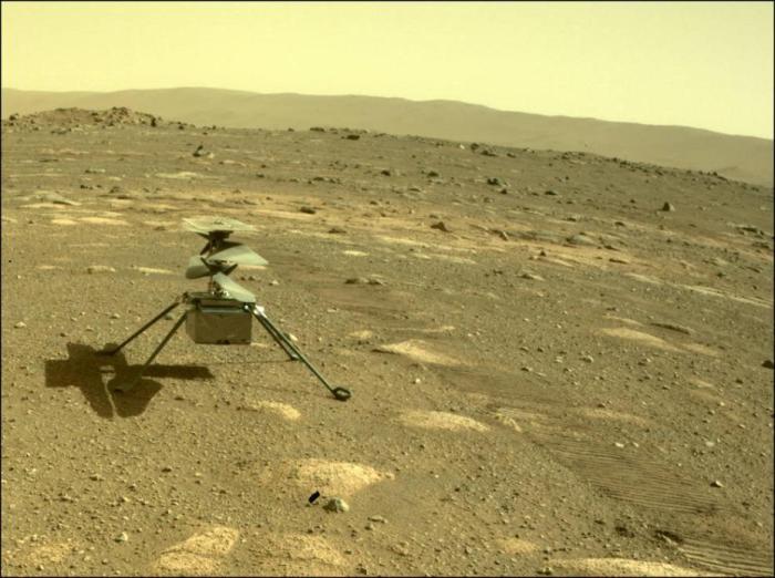 """当地时间2021年4月4日,美国国家航空航天局一架独创的直升机在飞行前降落在火星表面。美国国家航空航天局解释称:一架精巧的迷你直升机已降落在火星表面,为首次飞行做准备。这架超轻型飞机被固定在""""毅力""""号漫游者的腹部,该漫游者于2月18日在火星着陆。"""