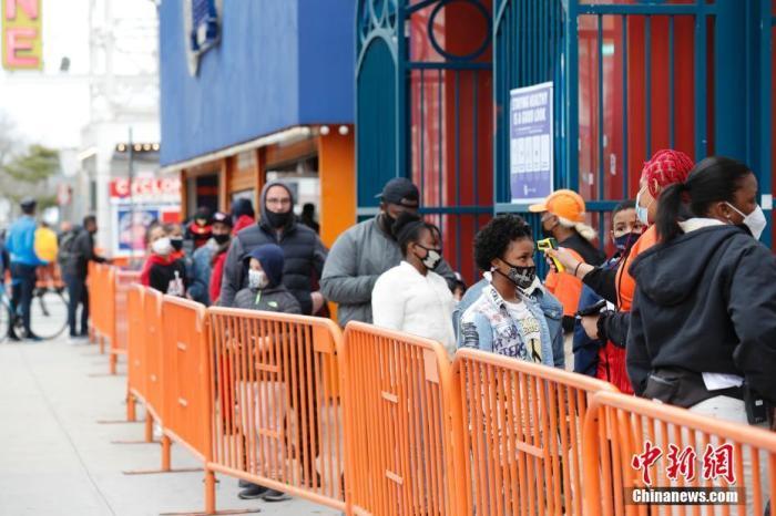 当地时间4月9日,美国纽约康尼岛游乐园重新开放,工作人员为排队入园的民众检测体温。当日,具有上百年历史的康尼岛游乐园在因新冠疫情关闭一年后重新开放。 中新社记者 廖攀 摄