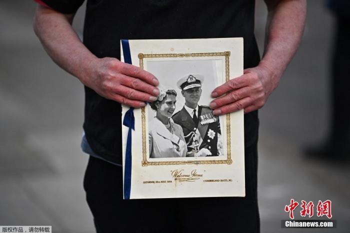 当地时间2021年4月9日,英国伦敦,英国白金汉宫发表声明称,菲利普亲王去世,享年99岁。民众手捧菲利普亲王的照片悼念亲王的离世。