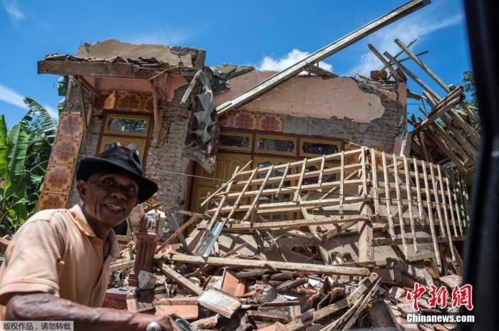 当地时间4月11日,印尼东爪哇南部海域发生6.1级地震后,市民骑车经过受损房屋。