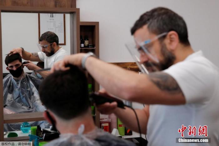 当地时间4月12日,英国赫特福德一家理发店恢复营业,理发师给顾客修剪发型。