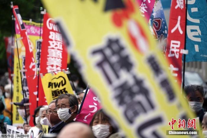 4月13日,日本政府正式决定,福岛第一核电站核污水经过滤并稀释后将排入大海。据日本共同社报道,13日上午日本首相菅义伟召开阁僚会议正式决定将福岛第一核电站污水排放入海。图为日本民众在日本首相办公室外举行抗议活动。
