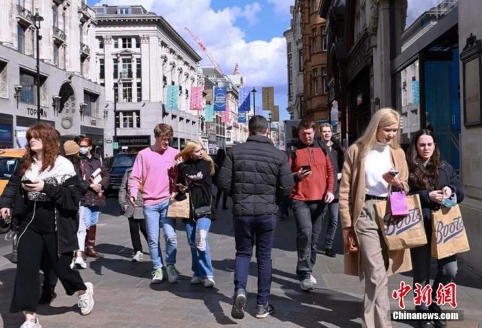 """当地时间4月12日,英国第三次全国性疫情封锁进入""""解封""""的第二阶段,非必需品商店、餐馆、酒吧、理发店和健身房等商业机构,经历了近三个月的关闭后,重新开业引来""""消费潮""""。图为伦敦市商业中心牛津街上人流涌动。<a target='_blank' href='http://www.chinanews.com/'>中新社</a>发 张梦琪 摄"""