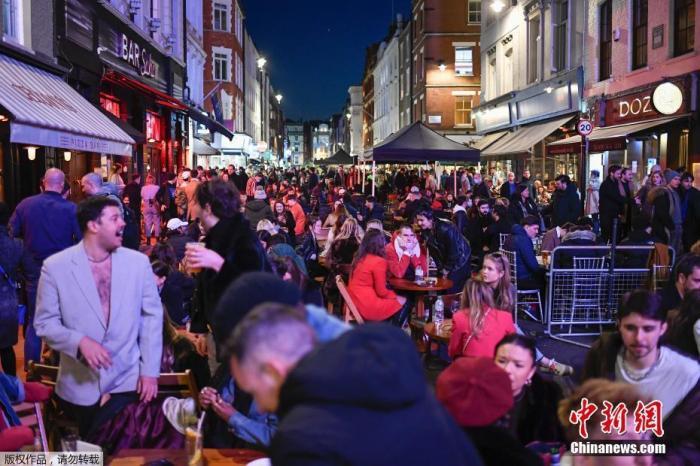 资料图:当地时间2021年4月12日,英国进入放松疫情封锁措施的第二阶段。商铺、理发店、健身房等被允许重新开张,酒吧和餐馆也可以在室外营业。据悉,酒吧解封的第一晚,伦敦大批民众在市中心喝酒跳舞,场面宛如狂欢节。