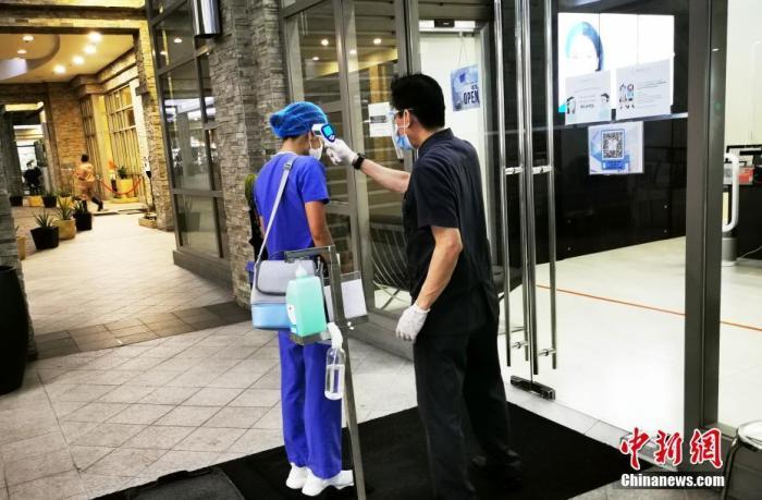 资料图:菲律宾马尼拉某牙医专科诊所护士戴着口罩、面罩,身着防护服,进入诊所前检测体温并进行手部消毒。<a target='_blank' href='http://www.chinanews.com/'>中新社</a>记者 关向东 摄