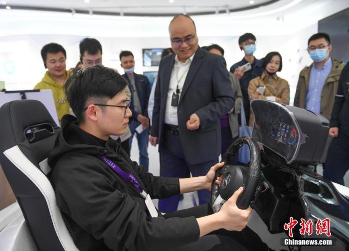 4月15日,浙江嘉兴,参观者在体验智能方向盘,该方向盘通过加装柔性电子感应设备,可对驾驶员的生理状态进行监测。中新社记者 王刚 摄