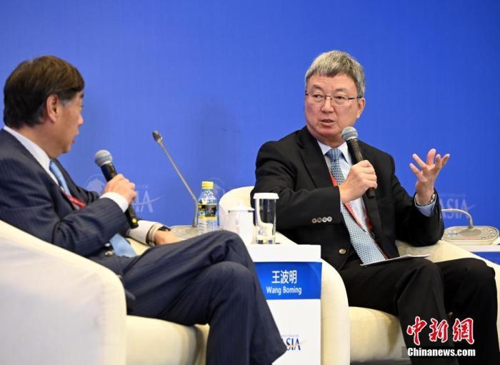 """4月19日,博鳌亚洲论坛2021年年会""""2021全球经济展望""""分论坛在海南省博鳌举行,清华大学国家金融研究院院长朱民(右)出席并参与讨论。 <a target='_blank' href='http://www.senbaojiuzhuang.cn/'>中新社</a>记者 侯宇 摄"""