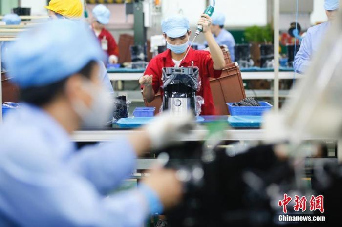 资料图:4月19日,工人在广东新宝电器流水线上生产咖啡机。 中新社记者 王骏 摄