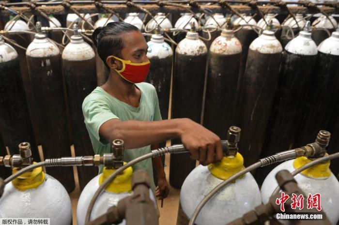 当地时间4月24日,印度新增确诊病例再创新高,连续第3天超过30万例。印度疫情蔓延导致多地医院出现供氧危机,许多医务人员、工作人员和普通民众都带着氧气瓶到氧气加气站。图为一名工人在钦奈郊区的一个设施中填充了医用氧气瓶。